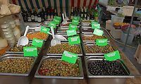 Wide display of different olives on French market stall. Bastille market, Paris, France.