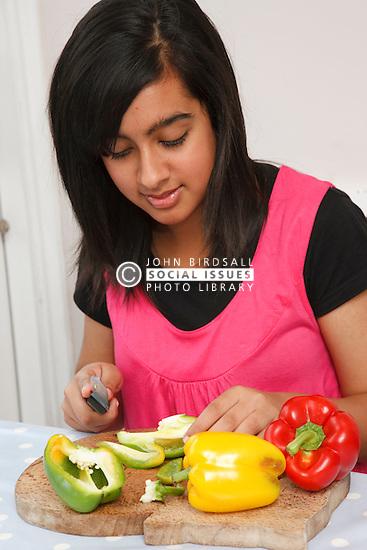 Teenage girl cutting peppers