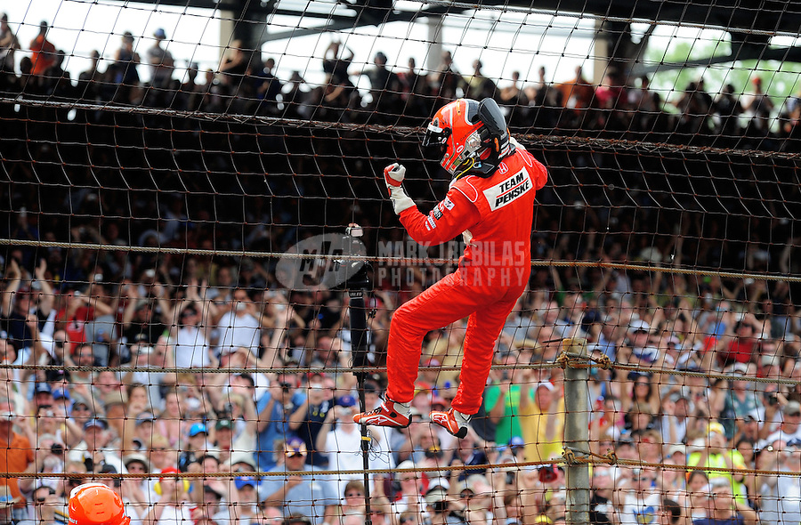 May 24, 2009; Indianapolis, IN, USA; IRL driver Helio Castroneves celebrates by climbing the fence after winning the 93rd running of the Indianapolis 500 at Indianapolis Motor Speedway.  Mandatory Credit: Mark J. Rebilas-