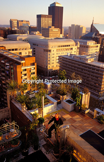 digajhb00173.Gauteng. Richard Yell, a landscaper, watering his plants on his rooftop terrace on June 18, 2002 in downtown Johannesburg, South Africa. Mr. Yell bought a penthouse apartment cheaply in a rundown building including this terrace, which he renovated. More and more people come to visit downtown Johannesburg, mostly known for its crime statistics and emptiness after dark. . Artists are moving to downtown Johannesburg to rent abandoned factories and great loft spaces for very cheaply. .©Per-Anders Pettersson /iAfrika Photos