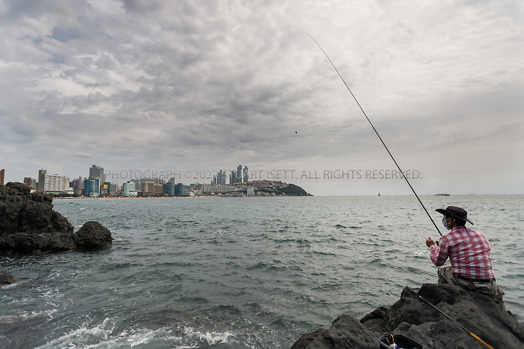 9/1/2013--Busan, South Korea<br /> <br /> A fisherman on the ricks of Dongbaek Island Park in Busan (Pusan) with Haeundae Beach behind.<br /> <br /> Photograph by Stuart Isett<br /> &copy;2013 Stuart Isett. All rights reserved.
