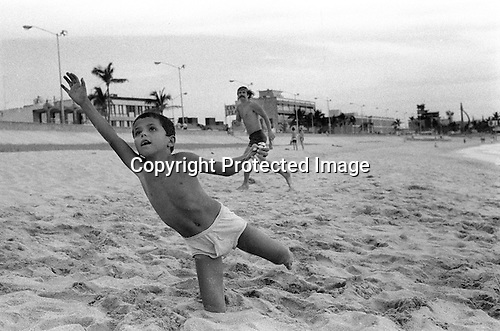 Mazatlan Mexico 1973. Local boy playing Frisbee with American men on beach. The boy is holding a small tame bird he has caught in his left hand.