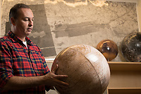UAA Professor and Director of Geological Sciences Dr. Simon Kattenhorn holds a model of Jupiter's Moon, Europa, the subject of his current work with NASA in his lab at UAA's ConocoPhillips Integrated Science Building.