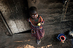 GALUFU, MALAWI OCTOBER 16: Magreti Nangamtani, age 3, eats a mango outside the family house on October 16, 2005 in Galufu, Malawi. Her mother, Stelia, age 26, and little sister Pilirani, age 2, are one of the poorest families in Galufu, and they have to beg for food every day Magreti has climbed a tree to find a mango to eat as the family doesn't have any maize to cook porridge. Most people in the village are poor and hungry, and cannot afford to buy maize at the market. The price is twice as much as the government subsidized prices. The government used to sell subsidized maize and fertilizer but not anymore. Many in the village eat mangoes and even boil unripe ones, as they cannot afford to buy anything else. The harvest was very bad in 2005 and the next one, due in April 2006 I uncertain because of lack of rains and drought. The village has seen an increase in poverty the last few years due to drought and HIV/Aids. Southern Africa has been hit by a severe hunger crisis due to drought and poverty. An ever-increasing HIV/Aids rate adds to the misery. Malawi is one of the worst hit areas and Galufu village is a typical small village that has become victim of this poverty spiral.  (Photo by Per-Anders Pettersson)