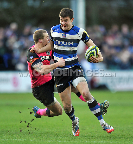 Ollie Devoto is tackled by Owen Williams. LV= Cup match, between Bath Rugby and Cardiff Blues on January 25, 2014 at the Recreation Ground in Bath, England. Photo by: Patrick Khachfe / Onside Images