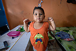 Samuel Alves da Silva, 3, poses as the Incredible Hulk in the one-room apartment he shares with his mother in Manaus, Brazil. The indigenous family migrated to the city in 2018, joining with other poor families to take over an unoccupied building--the Casa do Estudante--in the city center.<br /> <br /> Written parental consent obtained.