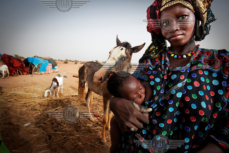 A woman stands next to her horse as she holds her baby at the UN refugee camp in Bani Bangou, having fled the violence in Mali between the government and radical Islamic militias.