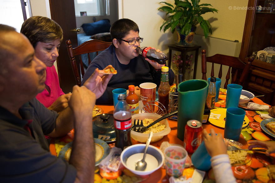 """Jorge drinks a Coca-Cola at a Sunday lunch at his family's home in Puebla, Mexico on April 23, 2017. Jorge Antonio Moreno Gaytán, a 34-year-old Mexican man, lives with his parents in Puebla, Mexico. He was diagnosed with Prader-Willi syndrome at age seven. He weighs 136 kilos (300 pounds) and stands 152 centimeters (4 feet 12 inches). Jorge is in the process of getting bariatric surgery. As a teenager, he would pawn his siblings' belongings in order to have money to buy food. He was also known to leave restaurants without paying. """"Our worst enemy is hunger, it's what will kill us"""", Jorge says. He is now part of a sports team for people with disabilities. He has been in a relationship for 11 years with, Maria Guadalupe Pilar Saucedo Granda, known as """"Lupita', also diagnosed with Prader-Willi syndrome. Prader-Willi Syndrome (PWS) is a rare genetic disorder caused by an abnormality in chromosome 15. Innewbornssymptoms includeweak muscle tone (hypotonia), poor appetite and slow development. In childhood the person experiences a sensation of constant hunger no matter how much he/she eats which often leads toobesityandType 2 diabetes. There may also be mild to moderateintellectual impairmentand behavioral problems. Physical characteristics include a narrow forehead, small hands and feet, short in stature, and light skin color. Prader-Willi syndrome has no known cure. However, with early diagnosis and treatment such as growth hormone therapy, the condition may improve. Strict food supervision is typically required. PWSaffects an estimated 1 in 10,000 to 30,000 people worldwide. (Photo by Bénédicte Desrus)"""