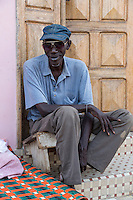 Senegal, Saint Louis.  Middle-aged Senegalese Man Sitting at his Front Door.