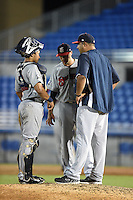 Brevard County Manatees pitching coach David Chavarria (48 in jacket) talks with pitcher Scott Lieser (15) and catcher Rafael Neda during a game against the Dunedin Blue Jays on April 23, 2015 at Florida Auto Exchange Stadium in Dunedin, Florida.  Brevard County defeated Dunedin 10-6.  (Mike Janes/Four Seam Images)