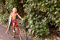 Young boy bikes with surfboard in hand near ehukai beach park on the north shore of Oahu.
