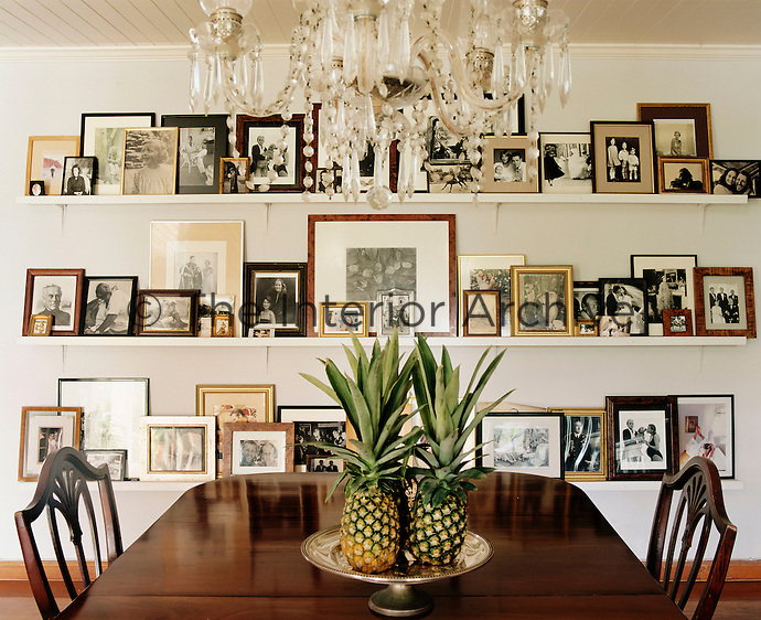 Open shelves in the dining room create an effective backdrop on which to display a collection of framed family photographs