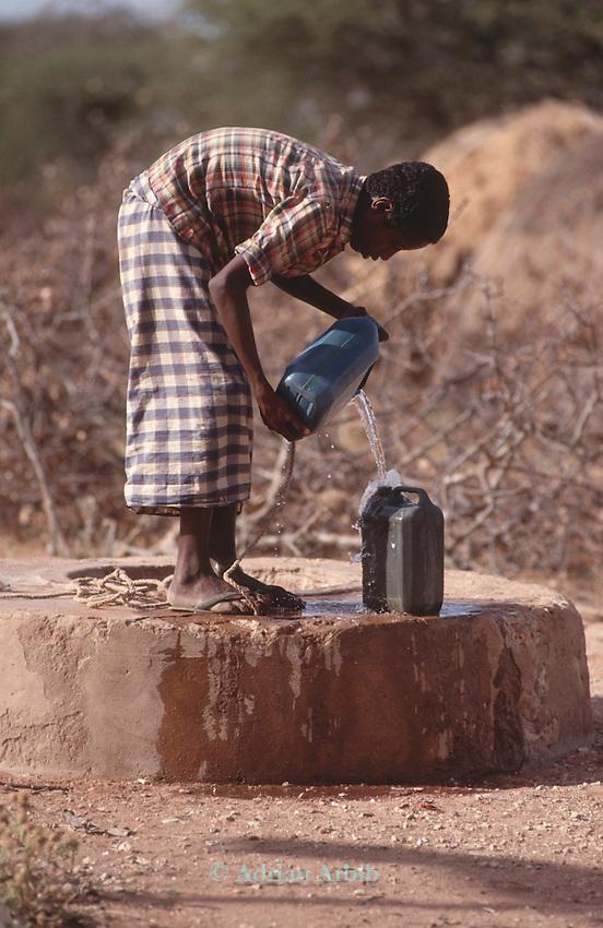 Somali boy filling water can from a borehole, Wajir, Somaliland, Kenya
