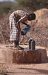 Somali boy filling water can from a borehole, Wajir, Somaliland, Kenya