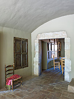 The living room opens into the dining room via a large stone archway