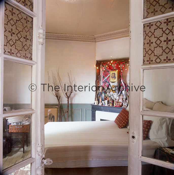A view through a pair of open French doors to a bedroom with a double bed. The room has original plaster cornicing and part painted panelling.