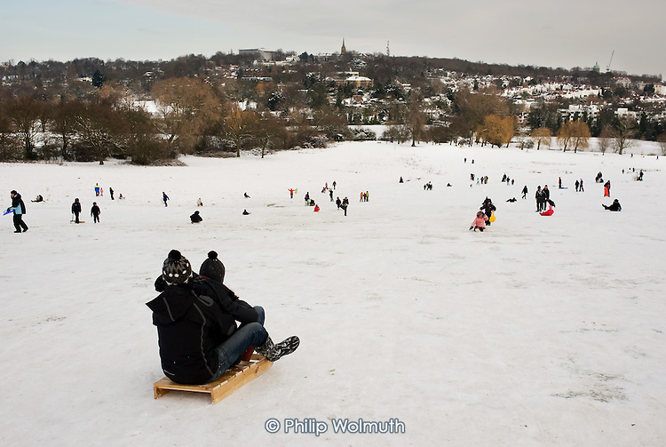 Children play in the snow on Parliament Hill, London.