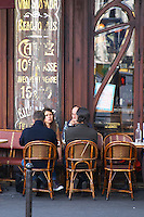 Le Bistrot du Peintre cafe bar terrasse terasse outside seating on the sidewalk. People sitting in chairs at tables eating and drinking outside at lunch time. In the background an old sign saying that coffee costs 10 ten cents, Beaujolais, Saumur The Bistrot du Peintre is an old fashioned Paris café cafe bar restaurant of art nouveau design with polished brass, mirrors and old signs
