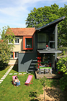 The owner relaxing on the lawn in front of the stunning contemporary rear extension to her traditional country cottage