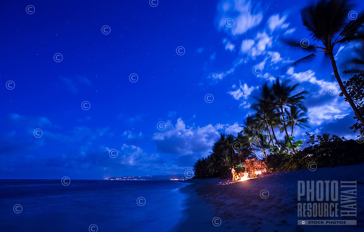Waialua residents enjoying a bonfire on a moonlit night on the beach next to a grass shack