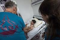 Sehid Xebat Hospital unter YPG-Verwaltung in Qamishli, Rojava/Syrien.<br /> Im Bild: Ein Arzt einer Recherche-Gruppe der Medizinischen Hilfsorganisation PHNX aus Deutschland untersucht Verletzte. Ein Kaempfer der YPG wurde in Kobane in die Lunge gschossen. Dabei wurden die Nerven des rechten Arm zerstoert. Eine weitere Kugel verletzte ihn schwer am Hals.<br /> 14.12.2014, Qamishli/Rojava/Syrien<br /> Copyright: Christian-Ditsch.de<br /> [Inhaltsveraendernde Manipulation des Fotos nur nach ausdruecklicher Genehmigung des Fotografen. Vereinbarungen ueber Abtretung von Persoenlichkeitsrechten/Model Release der abgebildeten Person/Personen liegen nicht vor. NO MODEL RELEASE! Nur fuer Redaktionelle Zwecke. Don't publish without copyright Christian-Ditsch.de, Veroeffentlichung nur mit Fotografennennung, sowie gegen Honorar, MwSt. und Beleg. Konto: I N G - D i B a, IBAN DE58500105175400192269, BIC INGDDEFFXXX, Kontakt: post@christian-ditsch.de<br /> Bei der Bearbeitung der Dateiinformationen darf die Urheberkennzeichnung in den EXIF- und  IPTC-Daten nicht entfernt werden, diese sind in digitalen Medien nach §95c UrhG rechtlich geschuetzt. Der Urhebervermerk wird gemaess §13 UrhG verlangt.]