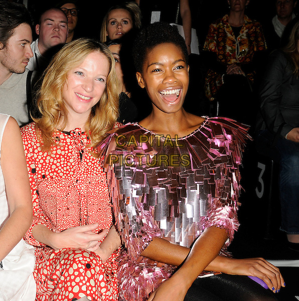 NATHALIE PRESS & TOLULA ADEYEMI.At the Issa Show, London Fashion Week Day 3, Somerset House, London, England, UK,.September 20th 2009..half length pink shiny fringed dress  futuristic tassels layered sitting red and cream print polka dot .CAP/CAN.©Can Nguyen/Capital Pictures.