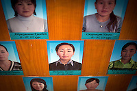 "A portrait of Dinara on the board of the ""The Best Students"" in the office of the president of the university in Naryn city where she studies Russian Literature and Turkish language. Dinara was kidnapped by Ahmat who wanted to marry her. After resisting for 5 hours, she finally accepted. 'I didn't know Ahmad well and didn't want to stay there. But I accepted because this is our tradition' Dinara says. Although illegal, bride kidnapping is common in rural parts of Kyrgyzstan. Dinara had a plan to move ot Turkey to work for a computer company 'My dream was to live in a city but I accepted because this is our tradition' she says. Each year around 16, 000 women become married after being kidnapped. They are known as 'Ala Kachuu' that translates as 'to grab and run away'. Defenders of the continuation of the practice sight tradition. However, during Soviet Times it was rare, and parents generally arranged marriages.."