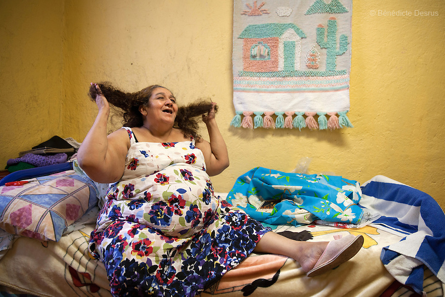 """María Isabel, a resident of Casa Xochiquetzal, in her bedroom at the shelter in Mexico City, Mexico on August 16, 2013. María Isabel, who grew up in Michoacán, Mexico, ran away from home at the age of 9 after a year in which her father """"used her."""" When she got to the Mexico City bus station, she met a woman selling tamales who offered her a home and education. María Isabel nearly finished her studies to become a teacher, but when her caretaker died, she became a sex worker at 17. She now reads, writes poetry, embroiders, and makes earrings and bracelets. Casa Xochiquetzal is a shelter for elderly sex workers in Mexico City. It gives the women refuge, food, health services, a space to learn about their human rights and courses to help them rediscover their self-confidence and deal with traumatic aspects of their lives. Casa Xochiquetzal provides a space to age with dignity for a group of vulnerable women who are often invisible to society at large. It is the only such shelter existing in Latin America. Photo by Bénédicte Desrus"""