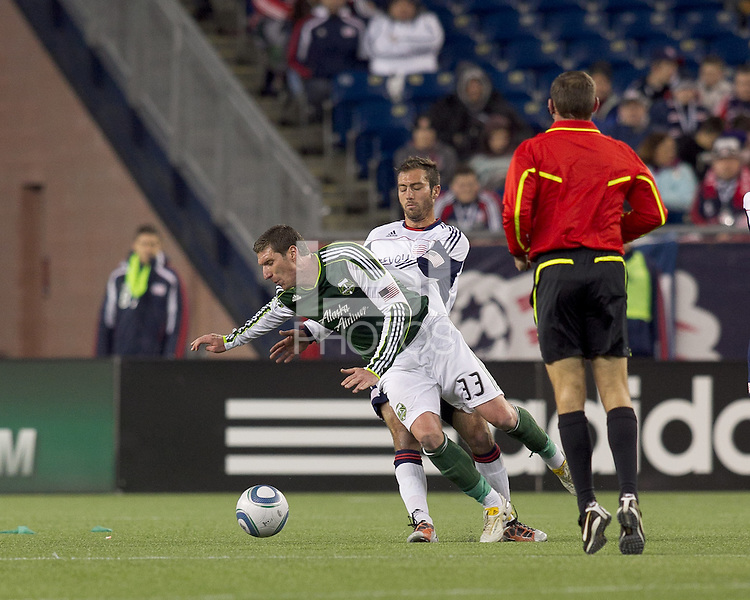 New England Revolution defender A.J. Soares (5) trips up Portland Timbers forward Kenny Cooper (33). In a Major League Soccer (MLS) match, the New England Revolution tied the Portland Timbers, 1-1, at Gillette Stadium on April 2, 2011.