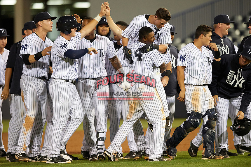 Tampa Yankees second baseman Nick Solak (39) gets picked up by Jorge Mateo (14) as teammates celebrate a walk off base hit during a game against the Fort Myers Miracle on April 12, 2017 at George M. Steinbrenner Field in Tampa, Florida.  Tampa defeated Fort Myers 3-2.  (Mike Janes/Four Seam Images)