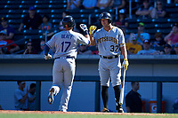 Glendale Desert Dogs first baseman Matt Beaty (17), of the Los Angeles Dodgers organization, receives a high five from teammate Logan Hill (37), of the Pittsburgh Pirates organization, after hitting a home run during an Arizona Fall League game against the Mesa Solar Sox on October 28, 2017 at Sloan Park in Mesa, Arizona. The Solar Sox defeated the Desert Dogs 9-6. (Zachary Lucy/Four Seam Images)