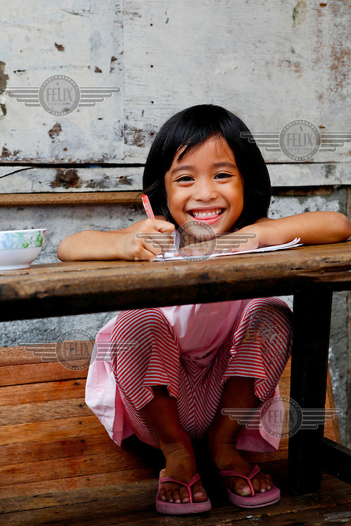 A young girl smiles as she does her homework on a table outside her home.