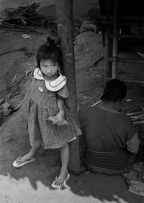 Young Karen girl and her mother in the Lep Per Her camp.  <br /> <br /> After the previous camp was burnt down by the Burmese military in 2002, the occupants were forced to live on the banks of the Moei river, being restricted in crossing into Thailand by the Thai military.  <br /> <br /> Even so, the teachers insisted that the children continue with their schoolwork and still held school everyday. &quot;We do our best and sacrifice all that we can because we have a vision for all these children to become educated people&quot; (volunteer teacher for IDP children).
