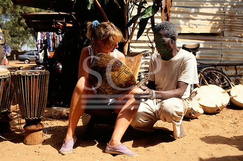 Banjul, Gambia. Female tourist bartering with a souvenir market trader over a wooden bowl.