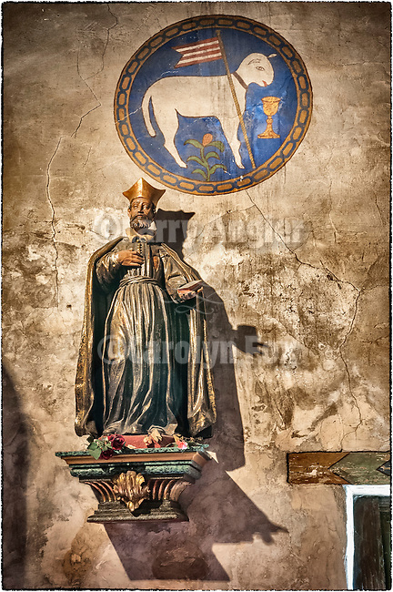 Statue of a saint beneath the Lamb of God painting, Carmel Mission, California.
