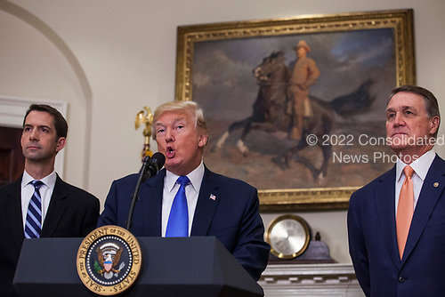 United States President President J. Donald Trump makes an announcement on the introduction of the Reforming American Immigration for a Strong Economy (RAISE) Act with US Senator Tom Cotton (Republican of Arkansas), left, and US Senator David Perdue (Republican of Georgia), right, in the Roosevelt Room at the White House in Washington, D.C., U.S., on Wednesday, August 2, 2017. The act aims to overhaul U.S. immigration by moving towards a &quot;merit-based&quot; system.  <br /> Credit: Zach Gibson / Pool via CNP