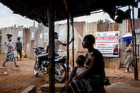 A poster on a wall in Kroo Bay states that ebola is a threat to peace and warns against virus spreading behaviours such as witchcraft and traditions such as washing the bodies of the dead.