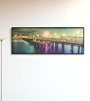 "Santa Monica Pier by Bill Brewer. Digital Print on Panel. Framed. 27"" x 73.5"",  Santa Monica Pier, California, in the evening with a lit Ferris Wheel"