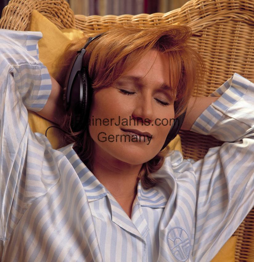 Junge Frau mit Kopfhoerern lehnt im Korbstuhl zurueck, die Augen geschlossen   young woman with headphones sitting in a cane chair, eyes closed