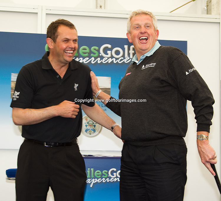 Andrew Coltart and Colin Montgomerie share a laugh as Colin takes plane in the putting challenge which was part of the Scottish Golf zone at Golf Live 2012 which took place at The London Club, Brands Hatch, Kent from 18th to 20th May 2012: Picture Stuart Adams www.golftourimages.com: 20th May 2012