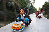 Sagor, a hawkerof chanachur (fried snacks), on the roof of a train near Gazipur. In Bangladesh many people ride on the roofs of trains as frequently that is the only space available. For others, the fares are too high and can be avoided or reduced by travelling on the roof. This practice has led to many hawkers plying their trade on train roofs too. However, riding on roofs and other parts of train exteriors leads to regular accidents, many of them fatal.