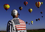 pvcMONBALOO1/10-3-05/JP2/ASEC.  Launch Director Steve Winters (CQ), of Albuquerque, watches from Balloon Fiesta Park field as balloonists approach during Monday morning's bag drop competition, photographed Monday Oct. 3, 2005.  Winters' wife Kristi Winters decorated Steve's head with stamp imprints of zebras.  (Pat Vasquez-Cunningham/Journal)