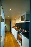 View down the length of the narrow kitchen with a glass panel which separates it from the dining area