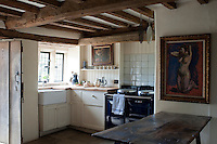 In the rustic kitchen an oil painting of a nude by Duncan Grant is displayed on the wall above an antique table