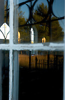 The setting sun reflects in windows and over Welsh language grave stones at the Moriah chapel in Trelew in Patagonian Argentina. Welsh immigrants tames the desolate land along the Rio Chubut in the 1860s. Their ancestors now embrace their Welsh roots in more than a dozen teahouses. (Kevin Moloney for the New York Times)