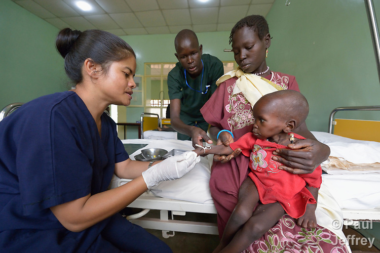 Ajok Uogu holds her malnourished 2-year old daughter Awok as Marilyn Sad, a nurse from India, installs an IV line in the child's arm in the St. Daniel Comboni Catholic Hospital in Wau, South Sudan. Nursing student Chol Chol looks on. <br /> <br /> Drought and armed conflict have pushed tens of thousands of people in Wau out of their homes, away from their farms, and unable to adequately feed themselves. The child was admitted to the hospital with severe malnutrition.<br /> <br /> Sad is a lay volunteer with Solidarity with South Sudan, which runs the Catholic Health Training Institute in Wau, where Chol is a student.