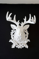 A white alabaster stag's head displayed on the black dining room walls creates a dramatic focal point