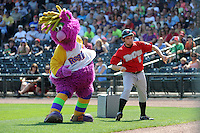 Great Lakes Loons guest Reggy the Purple Party Dude dances with an associate disguised as the first base coach during a game against the Fort Wayne TinCaps on August 18, 2013 at Dow Diamond in Midland, Michigan.  Fort Wayne defeated Great Lakes 4-3.  (Mike Janes/Four Seam Images)