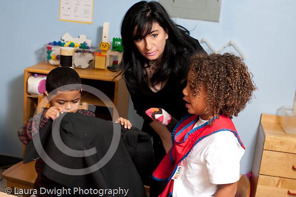 Education preschool 3-4 year olds SEIT teacher working with boy in classroom horizontal