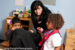 Education preschool 3-4 year olds SEIT teacher working with boy in classroom horizontal